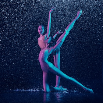 Two young female ballet dancers under water drops