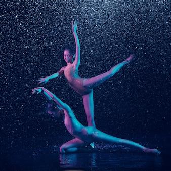 Due giovani ballerini femminili sotto le gocce d'acqua