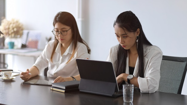 Two young female businesspeople working together in meeting room with office supplies