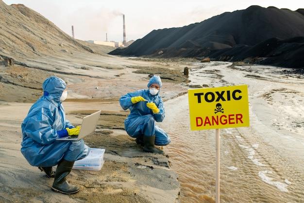 Две молодые женщины-экологи в защитных очках, очках и респираторах изучают характеристики токсичной воды на берегу реки