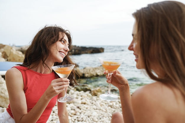 칵테일을 마시는 해변에서 피크닉을 하는 두 젊은 여자 친구 프리미엄 사진