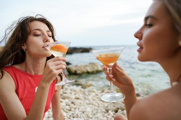 Две молодые подруги, пикник на пляже, пьют коктейли