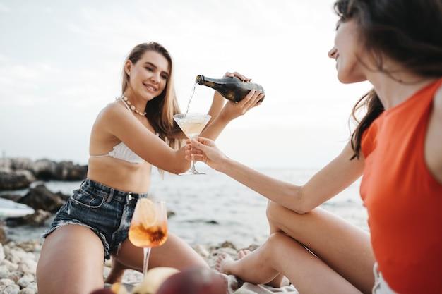 カクテルを飲みながらビーチでピクニックをしている2人の若い女性の友人