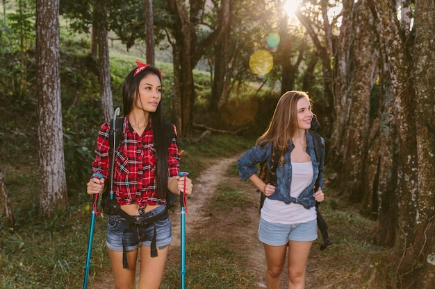 Two young female friends hiking in forest