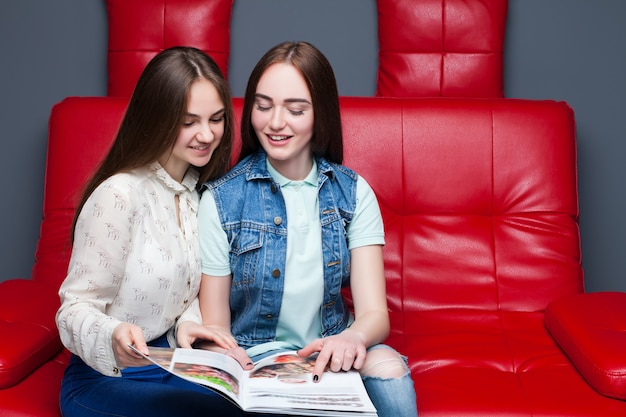Two young female friends look fashion magazine on red leather couch.
