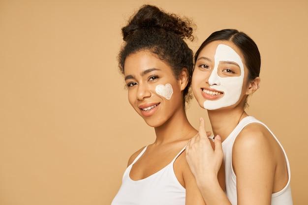 ベージュの背景の上に孤立した顔のマスクでポーズをとる2人の若い女性の友人。