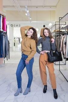 2人の若い女性の友人は、販売促進中に衣料品店で喜んで買い物をします