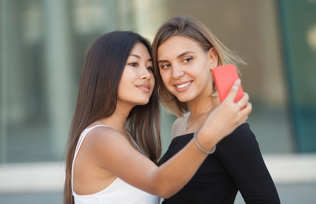 Two young female friends taking a picture of themselves on a smart phone.