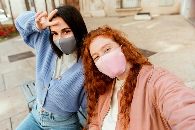 屋外で自分撮りをしているフェイスマスクを持つ2人の若い女性の友人
