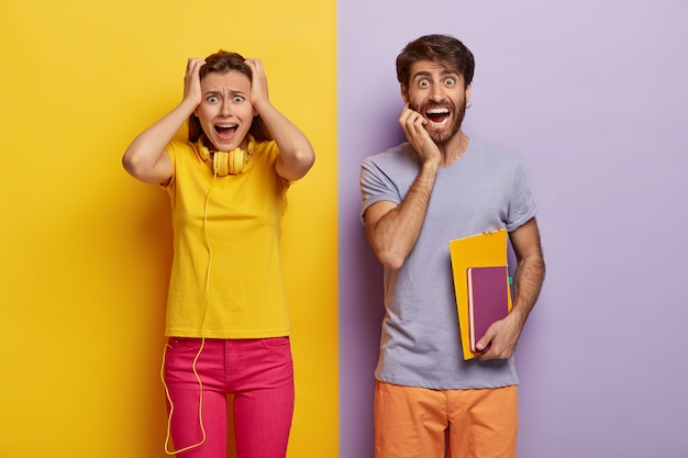 Two young female and male groupmates return back to studuing, woman stares with panic, keeps both hands on head, wears yellow t shirt and pink trousers, cheerful guy carries notepads for writing