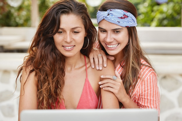 Two young female models sit in front of opened portable laptop computer, watch online broadcast and smile joyfully, support each other.