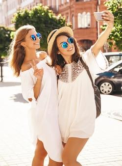 2人の若い女性の笑顔のヒッピーブルネットとブロンドの女性モデルは、電話でソーシャルメディアのselfie写真を撮る夏の白いヒップスタードレスを着ています。驚きの顔、感情、
