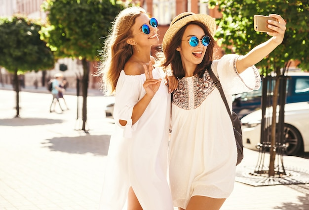 Two young female smiling hippie brunette and blond women models in summer sunny day in white hipster clothes taking selfie photos for social media on phone . showing peace