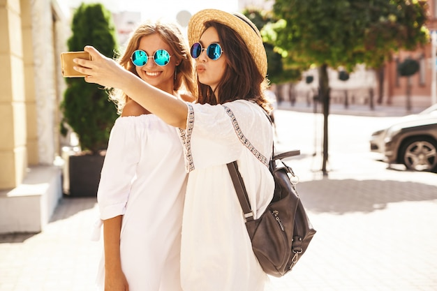 Two young female smiling hippie brunette and blond women models in summer sunny day in white hipster clothes taking selfie photos for social media on phone .