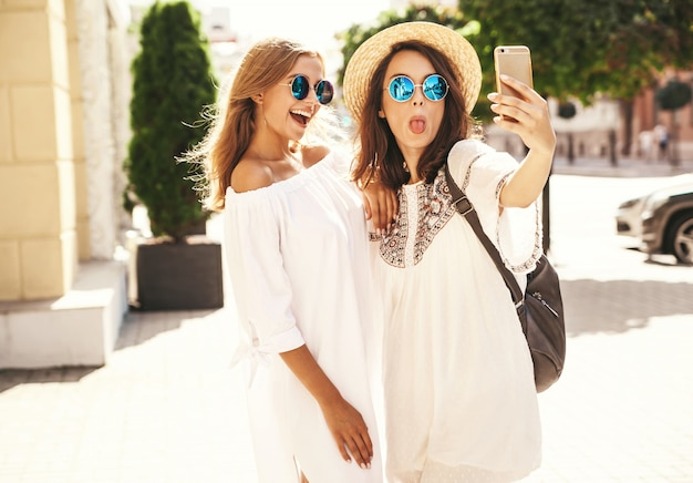 Two young female smiling hippie brunette and blond women models in summer white hipster dress taking selfie photos for social media on phone . surprise face, emotions,