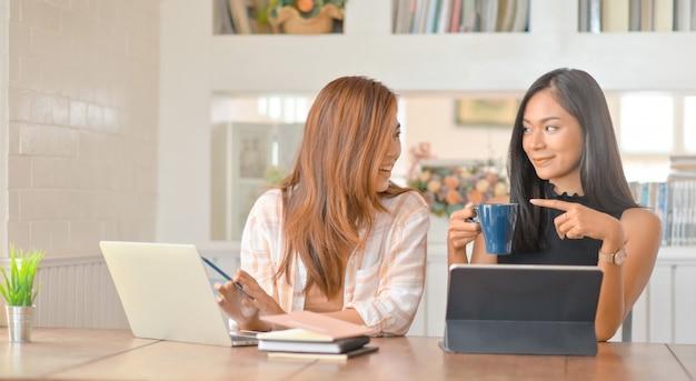 Две молодые студентки разговаривают с улыбкой и пьют кофе при создании отчета.