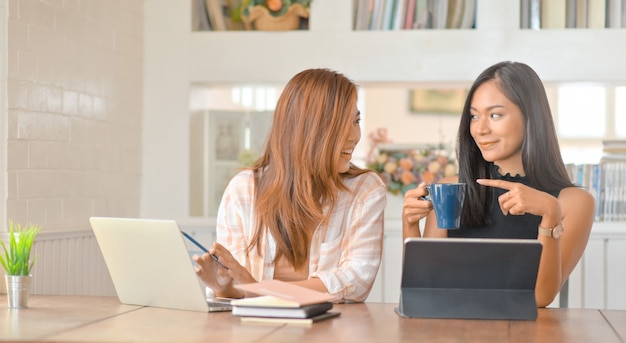 Two young female students talk with a smile and drink coffee while creating a report.