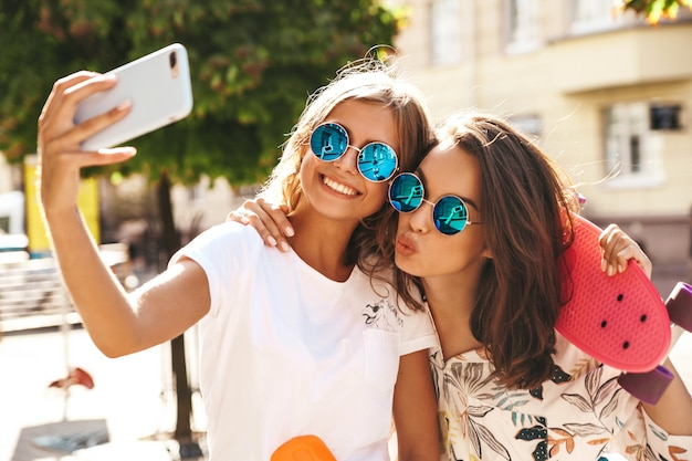 Two young female stylish hippie brunette and blond women models in summer hipster clothes taking selfie photos for social media on smartphone