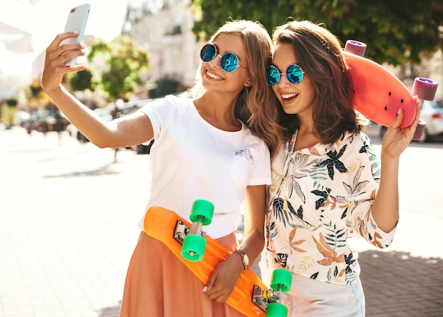 Two young female stylish hippie brunette and blond women models in summer sunny day in hipster clothes taking selfie photos for social media on phone . with colorful penny