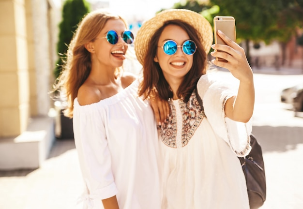 Two young female stylish hippie brunette and blond women models in summer sunny day in white hipster clothes taking selfie photos for social media on phone