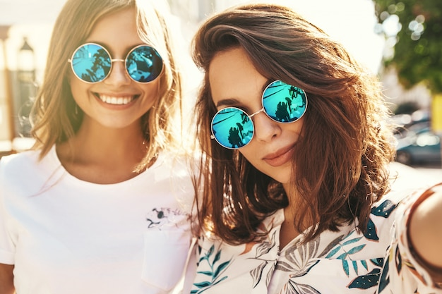 Two young female stylish hippie brunette and blond women in summer hipster clothes taking selfie
