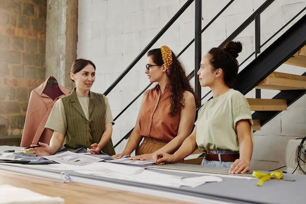 仕立てコーチにファッションアイテムの新しいスケッチを見せている2人の若い女性研修生
