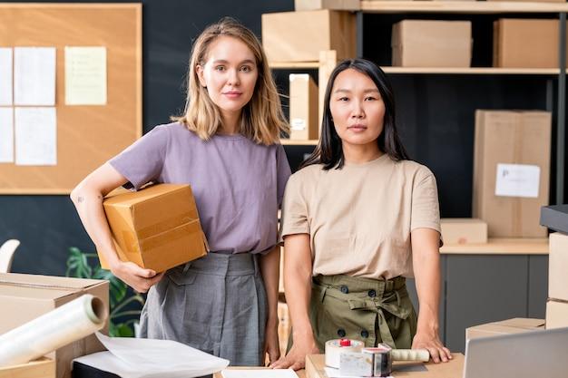 Две молодые работницы офиса интернет-магазина, стоящие за столом на полках с упакованными коробками и доской с документами