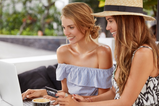 Two young females sit at outdoor cafeteria together, use modern portable laptop computer for shopping online with credit card payment, have cheerful looks, order new purchase, browse internet