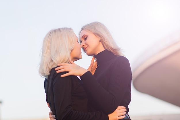 Две молодые женщины ходят, улыбаются, обнимаются и целуются на улице в городе