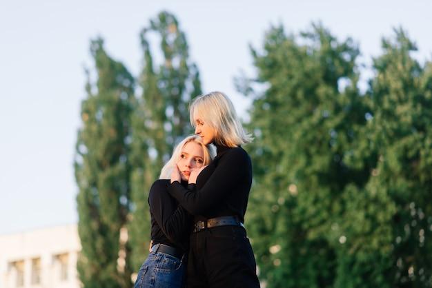 街の屋外で抱き合ったりキスしたりして笑顔で歩いている2人の若い女性