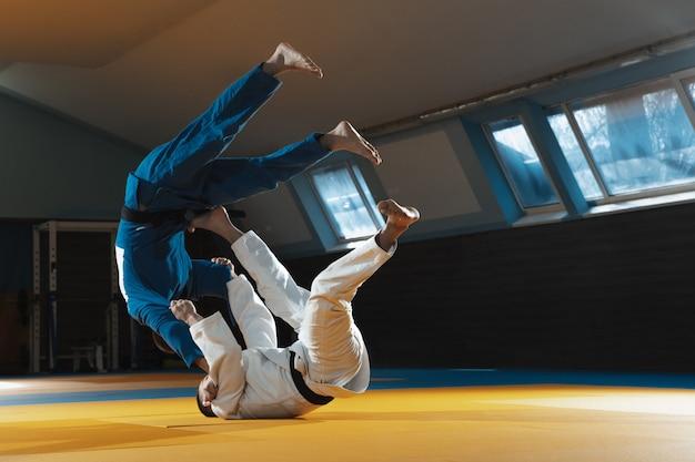 Два молодых бойца в кимоно тренируют боевые искусства в спортзале