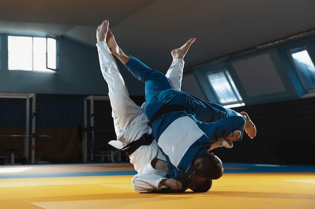 Due giovani combattenti in kimono allenamento arti marziali in palestra