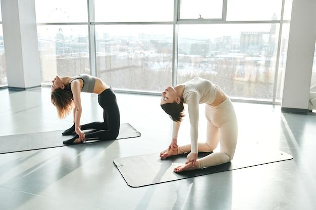 Две молодые подтянутые девушки в спортивной одежде наклоняются назад, стоя на коленях во время тренировки у большого окна тренажерного зала