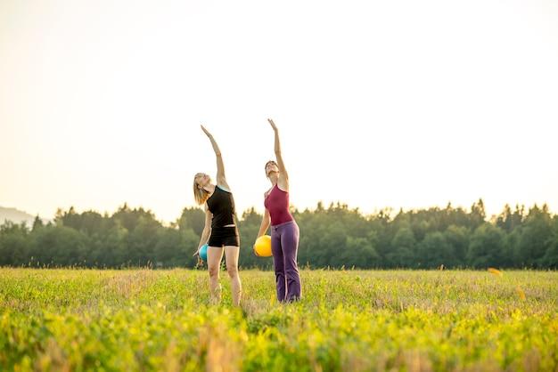 필라테스를하고 두 젊은 맞는 여성이 공중에서 한 팔을 들어 올리는 운동