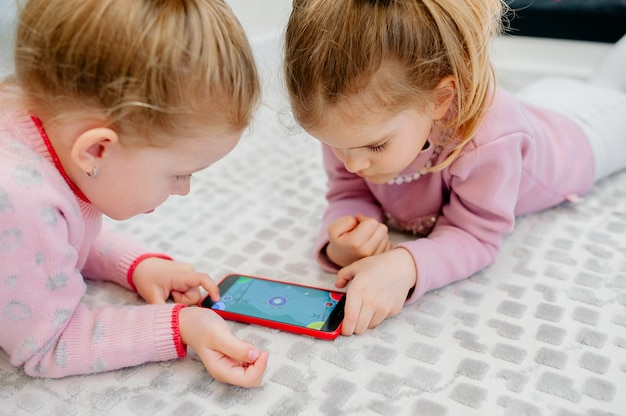 Two young focused children playing a smartphone with no name lying on the living room floor. young children and technology, sisters play with a mobile phone, watch videos or play games