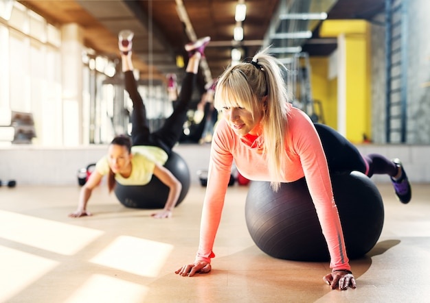 Two young focused girls in a gym using pilates balls for stretching after training.