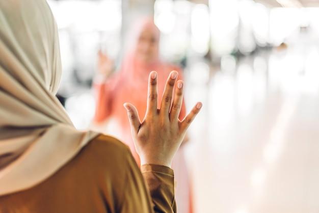 두 젊은 친구 이슬람 여성이 함께 인사를 나누며 인사를 나누며 즐거운 시간을 보내고 있습니다.
