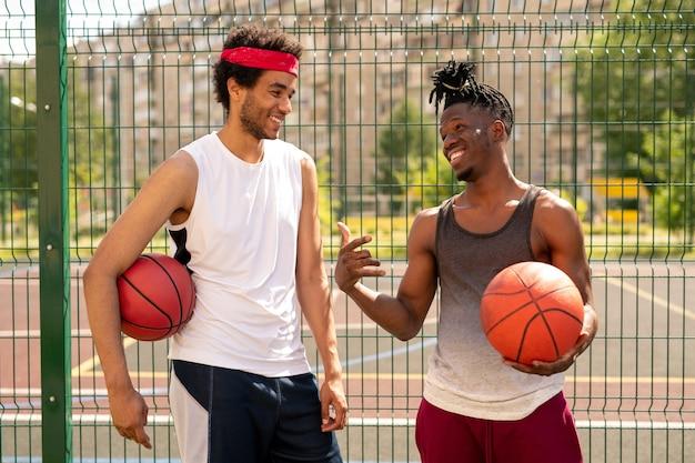 遊び場のフェンスのそばに立っている間にゲームのいくつかの奇妙な瞬間を議論する2人の若いフレンドリーなバスケットボールプレイメイト