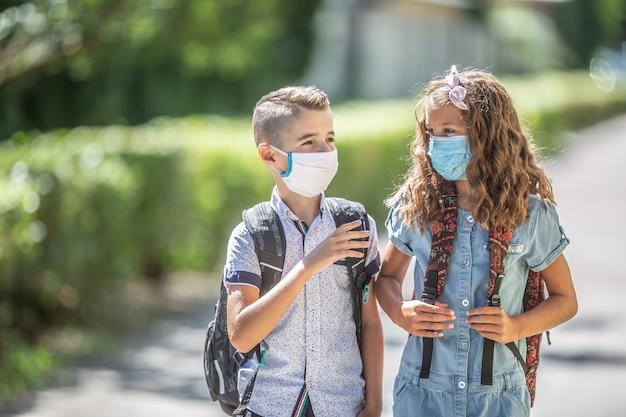 코비드-19 격리 기간 동안 마스크를 쓴 두 명의 어린 친구 반 친구가 학교에 가는 길에 대화를 나누고 있습니다.