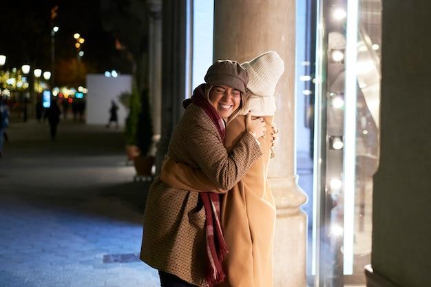 밤에 도시에서 두 젊은 친구가 포옹으로 서로 인사합니다. 그들은 겨울 옷을 입고 상점 창 앞에 서 있습니다.