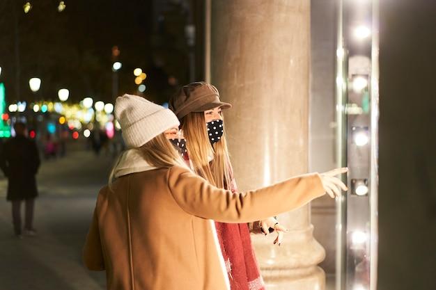 밤에 도시에서 상점 창에서 찾고 두 젊은 친구. 그들 중 하나는 무언가를 가리 킵니다.