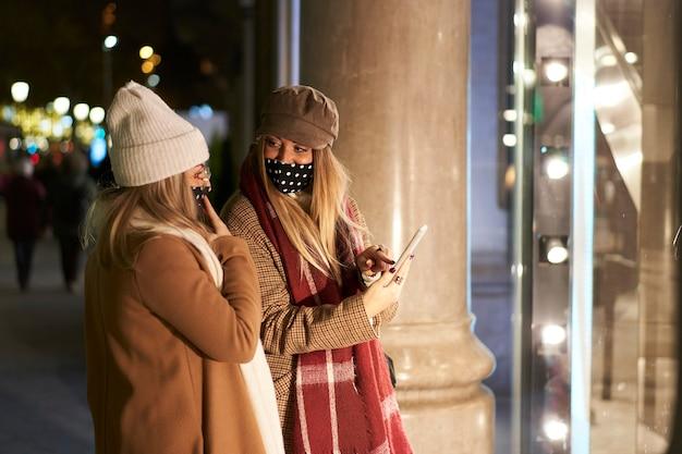 밤에 도시에서 상점 창에서 찾고 두 젊은 친구. 그들 중 하나는 친구에게 스마트 폰으로 무언가를 보여줍니다.