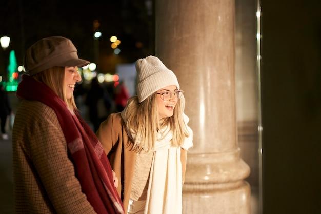 밤에 도시에서 상점 창에서 찾고 두 젊은 친구. 그들은 웃고 있고 즐거운 시간을 보내고 있습니다.
