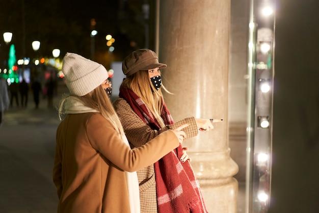 밤에 도시에서 상점 창에서 찾고 두 젊은 친구. 그들은 가게에서 무언가를 가리키고 있습니다.