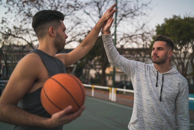 Двое молодых друзей играют в баскетбол.