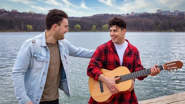 Due giovani amici che cantano e suonano la chitarra vicino a un lago in un parco
