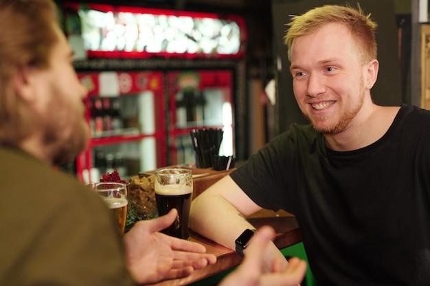 Два молодых друга сидят за барной стойкой, разговаривают друг с другом и отдыхают после работы