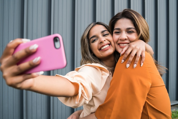 Two young friends smiling and taking a selfie with their mobile phone while standing outdoors. urban concept.