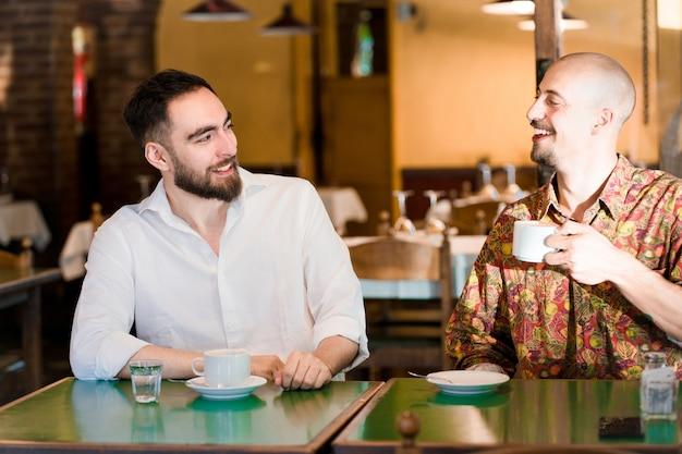 두 젊은 친구가 커피숍에서 커피 한 잔을 마시며 함께 시간을 보내고 있습니다.