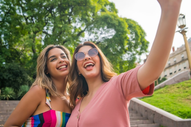Two young friends taking a selfie and smiling while standing outdoors. urban concept.
